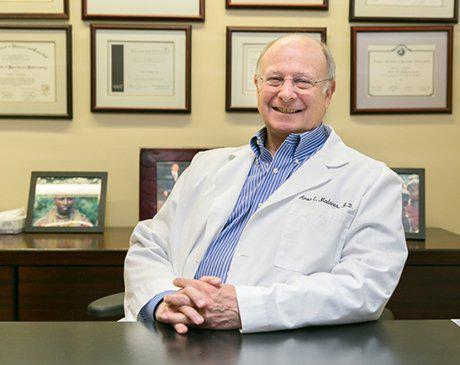 Dr. Madanes Sitting At Desk