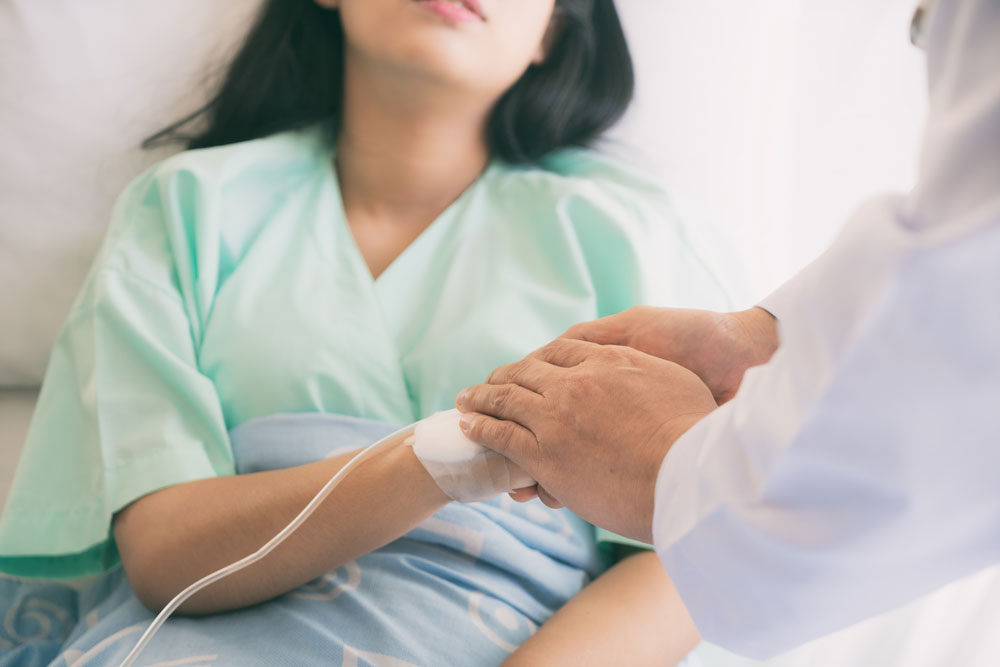 Doctor holding hand of sick woman